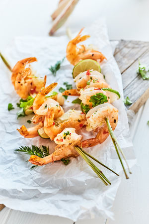 Gourmet seafood kebabs with spicy grilled prawns garnished with fresh herbs and lemon served on crumpled paper