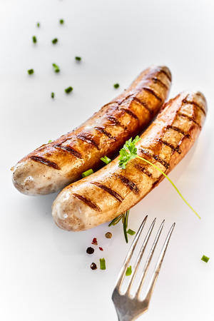 Two grilled sausages and a fork in close-up, served on white dish with leaf of fresh parsley and spices and viewed from above Imagens