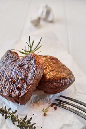 Two prime beef fillet medallions with fresh thyme and rosemary seasoned with black pepper and served on crumpled white paper in a close up presentation for a menu with copy space Imagens