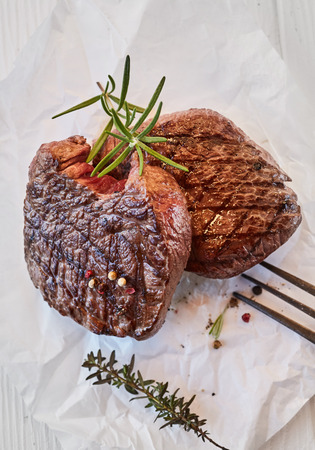 Two gourmet medallions of thick juicy grilled fillet beef steak seasoned with peppercorns and fresh thyme and rosemary on crumpled white paper, suitable for a menu