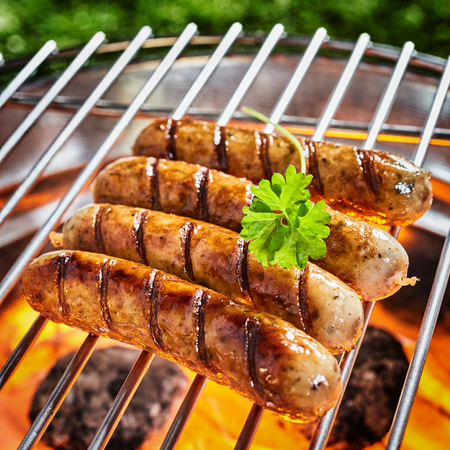Four grilled sausages on grid barbecue grill outdoors decorated with fresh green leaf of parsley, viewed in close-up