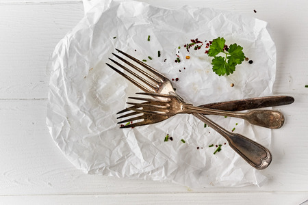 Three vintage silver fork on crumpled white paper with scattered seasoning and fresh parsley after eating a meal viewed top down from above