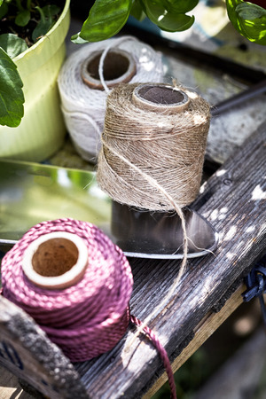 Three colored balls of twine made from natural hemp and jute lying on a garden table outdoors with a small trowel and flowerpot
