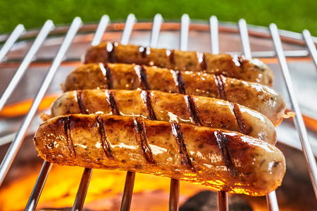 Delicious and hot grilled sausages in close-up on grid grill outdoors