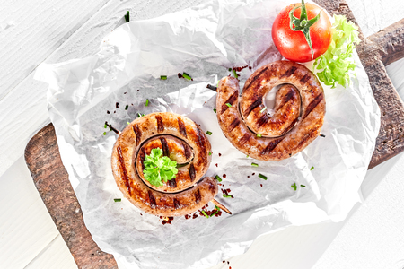 Delicious grilled or barbecued beef sausages served in two coiled portions on crumpled paper on an old vintage board with salad trimmings viewed from overhead Imagens