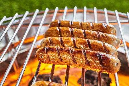 Four juicy pork sausages grilling on a BBQ over the hot coals in a close up view over a green grass backdrop