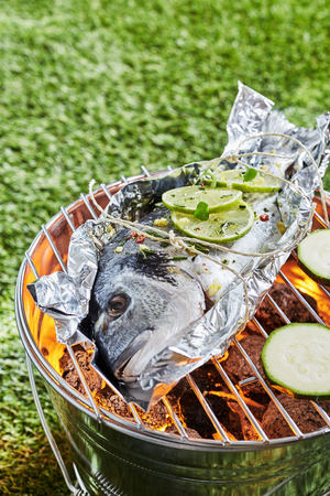 Whole fresh raw fish grilling on aluminium foil over a hot fire in a barbecue outdoors in a park or garden in summer