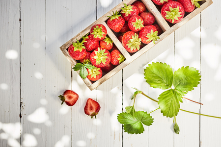 Fresh ripe red strawberries in a divided wooden box on a table outdoors at farmers market viewed top down