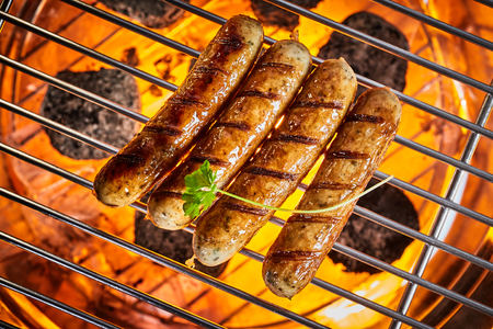 Grilled sausages on hot grill from above with a leaf of fresh parsley. Full frame close-up overhead shot Imagens
