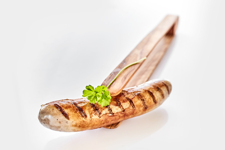 Single grilled pork sausage garnished with fresh parsley presented with wooden bamboo thongs over white with copy space