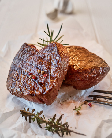 Two thick lean portions of beef fillet steak with fresh thyme and rosemary and seasoned with black pepper and salt served on crumpled white paper