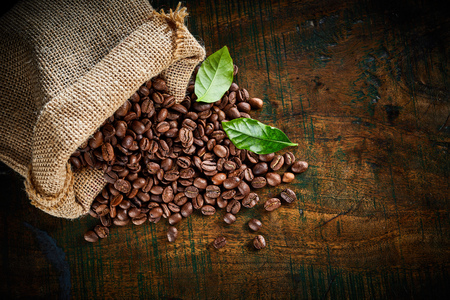 High angle view of fresh roasted coffee beans spilling from a hessian sack onto vintage wood with two green leaves, copy space and vignette