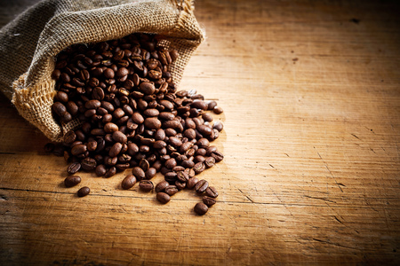 Fresh roasted coffee beans spilling from a hessian sack onto a rustic wood background with copy space and vignette