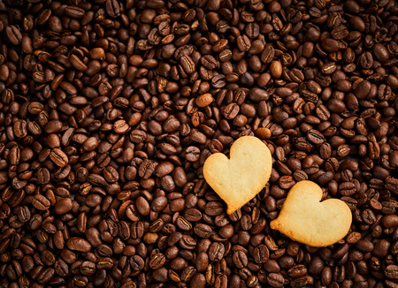 Roasted coffee bean background with fresh pastries or heart-shaped biscuits in the corner conceptual of love, like, friendship or Valentines Day