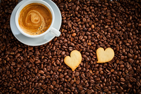 Two heart shaped cookies with cup of hot frothy espresso coffee on a background of roasted brown coffee beans viewed top down in a conceptual image Imagens