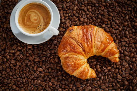 Roasted coffee bean background with cup of hot frothy espresso coffee and a flaky freshly baked croissant in a concept of a continental breakfast or coffee break Imagens