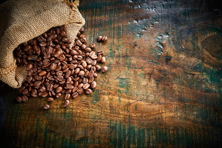 Small hessian bag of fresh roasted coffee beans spilling onto an old rustic wood surface with copy space viewed from above