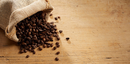 Small rustic burlap bag of speciality blended roasted coffee beans spilling onto a wooden background with copy space in panorama banner format