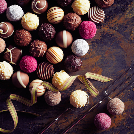 Large selection of luxury handmade pralines with decorative chocolate balls displayed with a wire fork and lifter on old vintage wood in square format