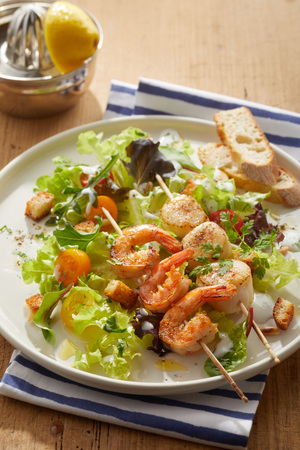 Grilled spicy scampi or baby lobster tails with scampi served on wooden skewers on a bed of leafy salad greens with crunchy fried croutons and sliced baguette