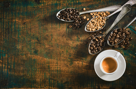 Espresso coffee with assorted roasted coffee beans displayed spilling from vintage silver spoons onto a rustic wood table with copy space viewed from above Фото со стока