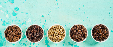 Panorama banner with fresh full and medium roasted and raw coffee beans in individual bowls on a mottled blue green background with copy space
