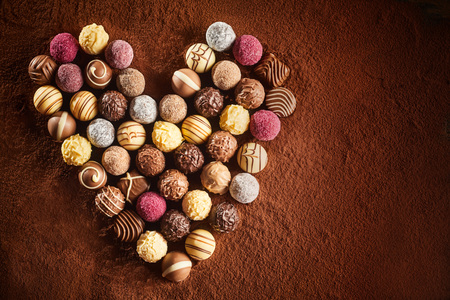 Valentines chocolate assortment in a heart shaped still life on a bed of cocoa powder with copy space for your greeting