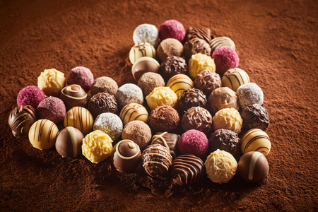 Heart shaped layout of various fancy chocolate candies sitting on surface of brown cocoa powder viewed in close-up Stock Photo - 123183626