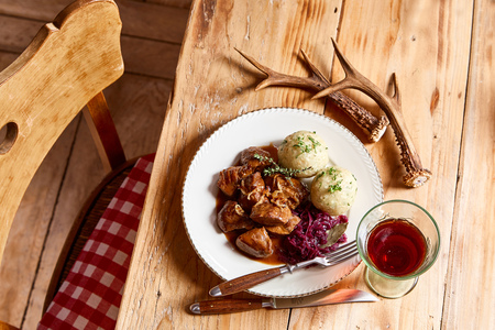 Serving of wild venison goulash with deer antlers accompanied by dumplings and red cabbage on a rustic table viewed from overhead