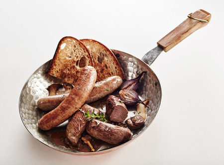 Assorted wild venison sausages with rye toast and herbs served in a copper pan high angle over white with copy spave Stok Fotoğraf