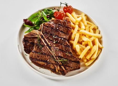 Seasoned marinated grilled T-bone steak with French Fries, salad greens and roasted tomatoes served on a plate viewed high angle