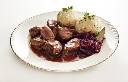 Tasty wild venison goulash in a rich gravy served with German dumplings and shredded red cabbage in a low angle view on a plate on white