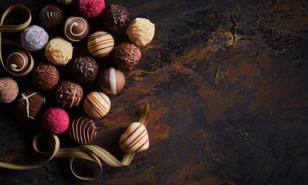 Banner rustico con cioccolatini di lusso fatti a mano e una pralina a forma di cuore su un nastro dorato che rotea su legno testurizzato con vignetta e spazio di copia