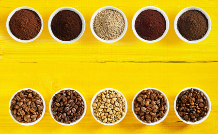 Double border of a selection of different raw and roasted beans and ground coffee in separate bowls arranged neatly top and bottom with central copy space on a yellow wood background
