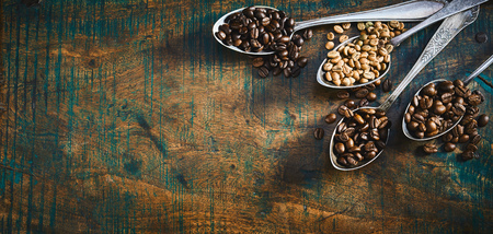 Assorted roasted and raw coffee beans displayed in the corner in vintage silver spoons overflowing onto a rustic wood table in a panorama banner with copy space Stok Fotoğraf