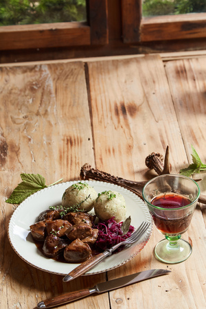 Wild venison goulash in a rich gravy served with a glass of red wine on a table decorated with deer antlers with copy space Stock Photo