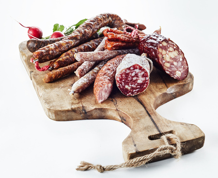 Large selection of spicy dried and smoked sausages on an old wooden chopping board isolated on white in a concept of regional German cuisine Archivio Fotografico