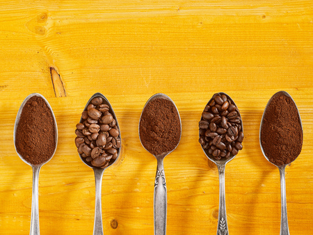 Assorted single origin coffee displayed in vintage silver spoons with roasted beans and fresh grounds over a yellow wood background with copy space