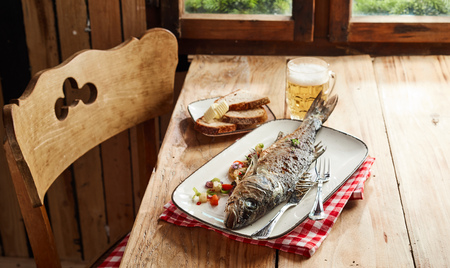 Savory oven roasted whole sea bass with herbs served on a large plate at a rustic tavern table with a cold frothy beer