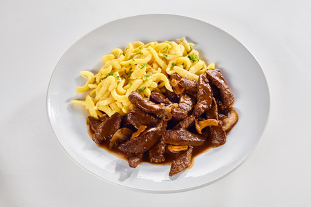 Serving of tasty Swiss ragout with the meat cut into fine strips served in a rich gravy with mushrooms and noodles isolated on white for menu advertising Zdjęcie Seryjne