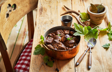 Vintage copper pot with spicy venison goulash on a table decorated with green leaves, utensils, red wine and a pair of wild deer antlers Stockfoto