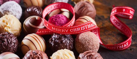 Red festive Merry Christmas ribbon twirled over a selection of different gourmet handmade chocolates in panorama banner format