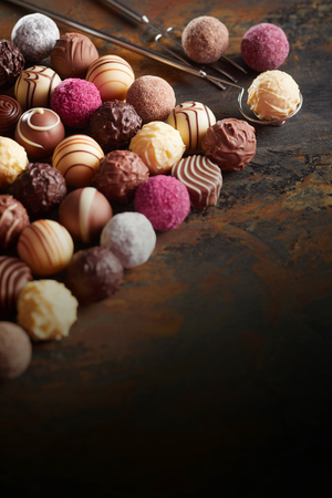 Luxury chocolate pralines in neat diagonal lines arranged on dark rustic wood with corner copy space in vertical format