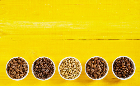 Border of an assorted variety of single origin raw and roasted coffee beans in bows on an exotic yellow wood background with copy space