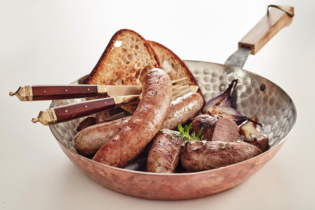 Copper pan with assorted German sausages served with rye bread toast and utensils over white