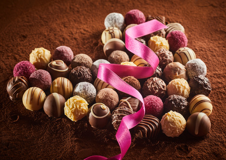 Heart shaped layout of luxury chocolate candies with pink silk ribbon over cocoa powder surface, viewed in close-up from high angle Stock Photo