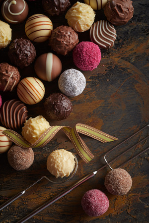 Selection of speciality gourmet chocolate balls or pralines in rows on rustic vintage wood with wire fork and lifter Stock Photo - 123184256