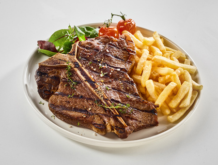 Barbecued T-bone steak with pommes de frites and fresh greens seasoned with herbs and served on a plate over white for menu advertising Stock Photo