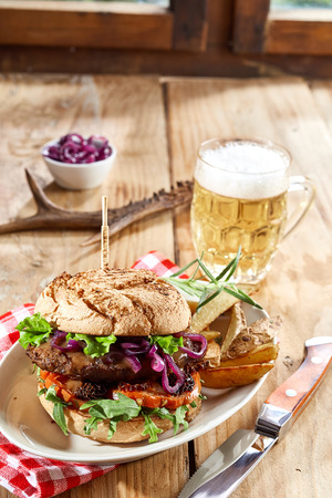 Wild venison beef burger with salad trimmings served on a plate with potato wedges and a cold frothy beer on a rustic table, side view for menu