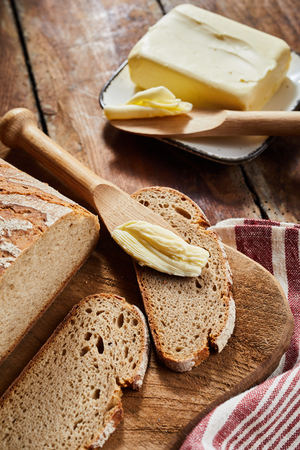 Loaf of rye bread with cut slices on a board with a wooden knife or butter spreader and pat of farm fresh butter on a plate alongside Banco de Imagens